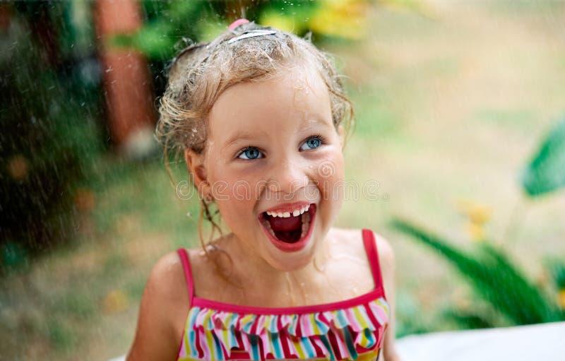 Близкий поднимающий вверх портрет счастливой милой маленькой девочки насладиться дождем лета стоковое изображение