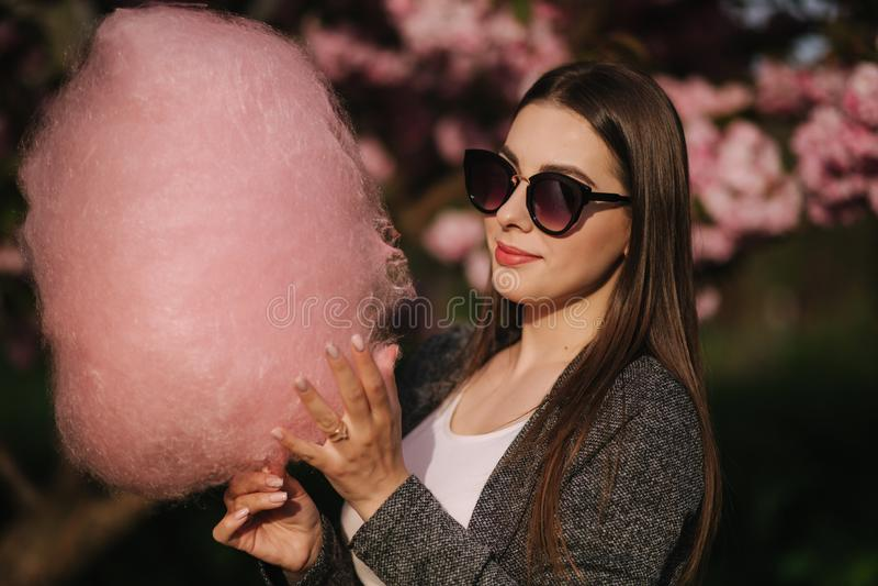 Близкий поднимающий вверх портрет усмехаясь девушки держа конфету хлопка в руках Девушка одетая в блейзере и солнечных очках grre стоковая фотография