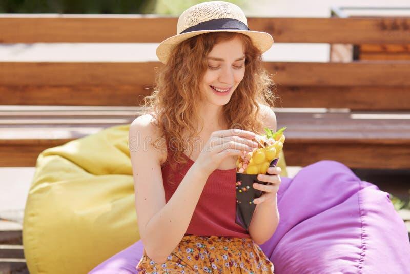 Близкий поднимающий вверх портрет хорошего выглядящ нежной девушкой сидя на сумке фасоли снаружи, держащ еду в обеих руках, усмех стоковая фотография rf