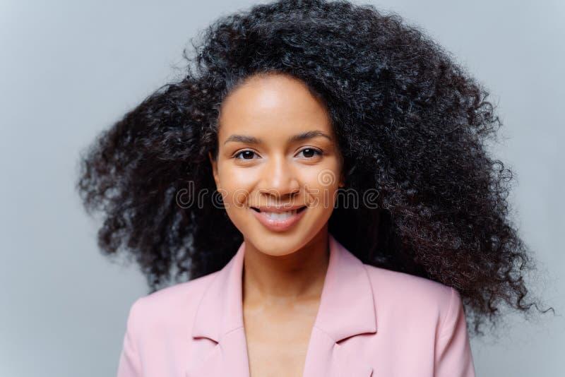 Близкий портрет изящной счастливо-шерстяной преуспевающей бизнес-леди, одетой формально, имеет вьющиеся роскошные волосы, улыбки стоковое изображение