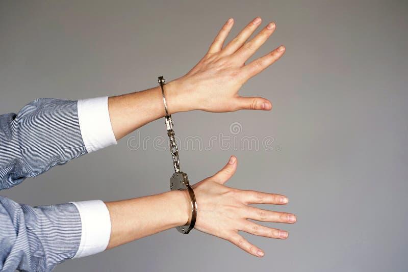 близкий преступник надевает наручники руки зафиксированные вверх по взгляду стоковое фото rf
