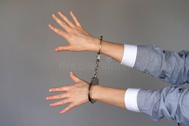 близкий преступник надевает наручники руки зафиксированные вверх по взгляду стоковые фотографии rf
