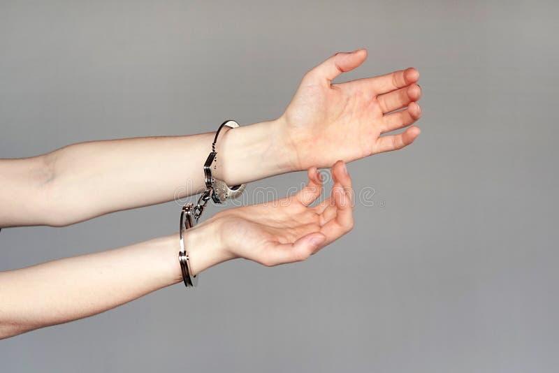 близкий преступник надевает наручники руки зафиксированные вверх по взгляду стоковая фотография rf