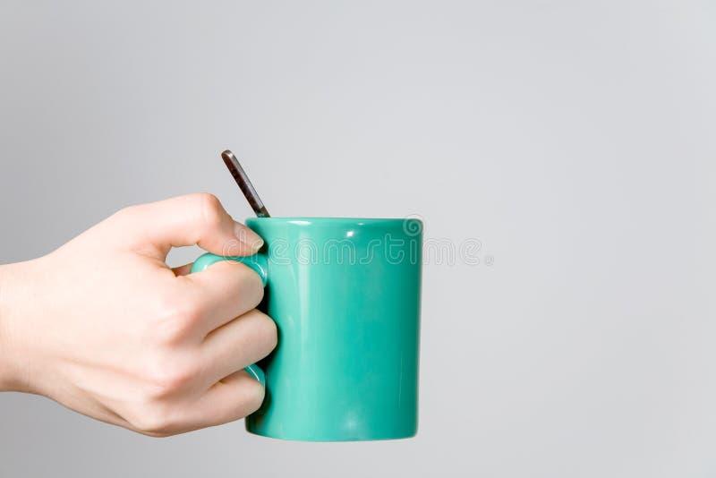 близкий чай ложки удерживания руки чашки вверх по женщине стоковое фото rf