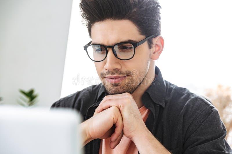 Близкое поднимающее вверх изображение сконцентрированного серьезного красивого человека в eyeglasses стоковое фото rf