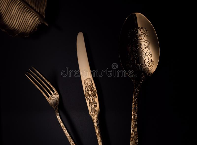 Близкое поднимающее вверх изображение с ложкой, ножом, вилкой и золотым аксессуаром на таблице иллюстрация штока