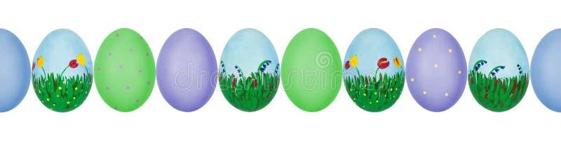 Близкое поднимающее вверх фото красочной руки покрасило пасхальные яйца с текстурой eggshell в ряд картина безшовная стоковые фото