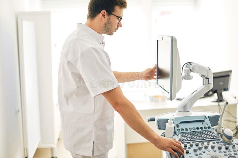Близкое поднимающее вверх фото машины ультразвука мужского доктора работая стоковые изображения rf