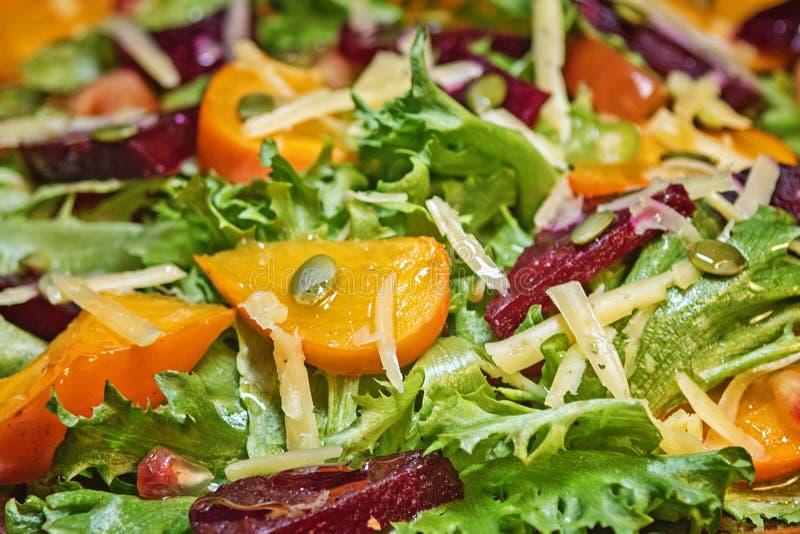 Близко - вверх очень вкусного салата осени с хурмой шоколада, салатом, томатами, гранатовым деревом, взглядом сверху Вегетарианск стоковое изображение rf