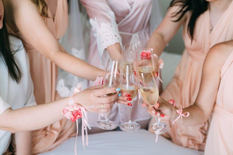 Близко вверх, руки девушек со стеклами шампанского празднуют начало свадьбы стоковое фото