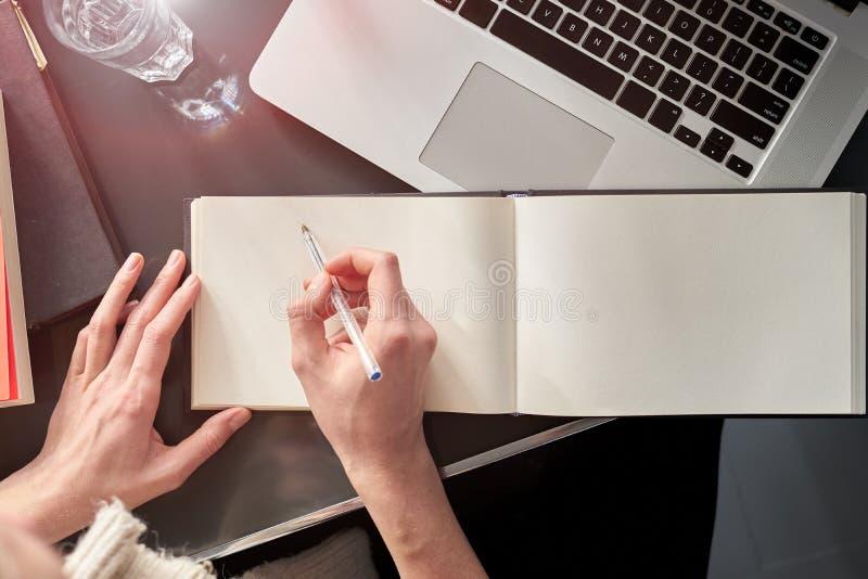 Близко вверх рук женщины делая примечания на белой распространенной книге Молодая женщина или студент работая и писать на тетради стоковая фотография rf
