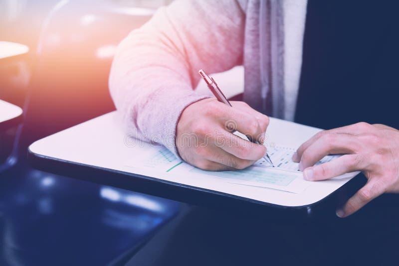 Близко вверх, экзамены карандаша удерживания студента средней школы писать в классе для теста образования, копируют космос для ва стоковая фотография rf