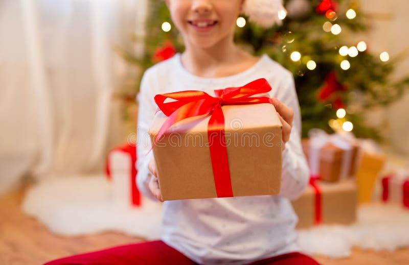 Близко к девушке с подарком на Рождество дома стоковые фото