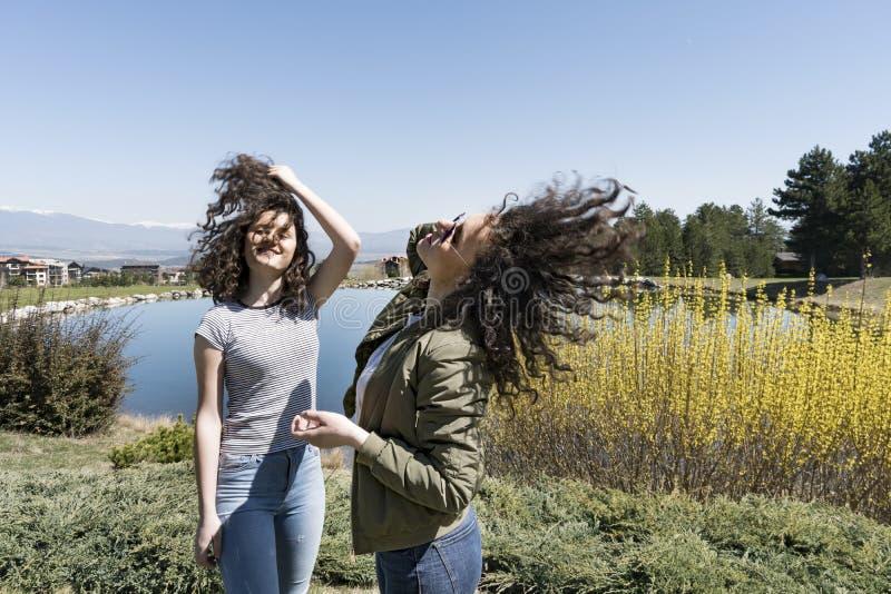 2 близнеца девушек держа вьющиеся волосы развеванный ветром стоковые фотографии rf