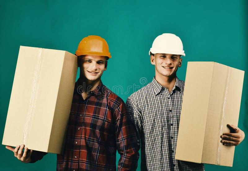 Близнецы с коробками владением шлемов Поставка и moving концепция стоковое фото rf