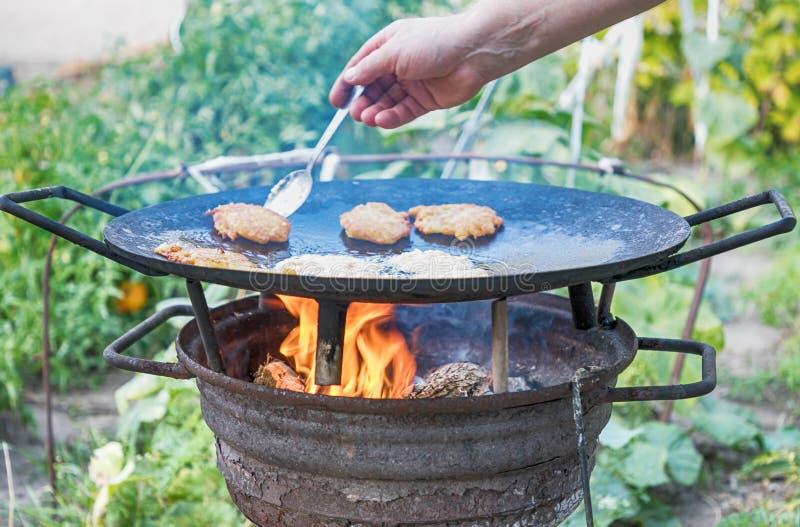 Блинчики картошки зажарили в масле на предпосылке природы Подготавливать еду на лагерном костере в одичалый располагаться лагерем стоковое изображение