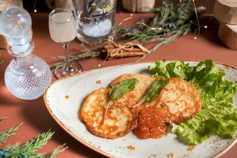 Блинчики картошки с йогуртом и красные блинчики икры с икрой стоковое изображение
