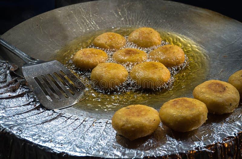 блинчики картошки frizzle в черной сковороде стоковые изображения