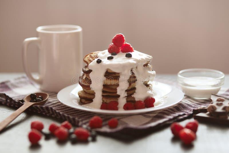 Блинчики на темном деревянном столе украшенном с ягодами, ложкой, чашкой с кофе или чаем, поленикой и голубикой, вкусным завтрако стоковое фото rf