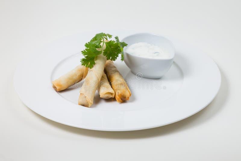 Блинчики с начинкой и погружение на белой плите на белой предпосылке стоковое фото
