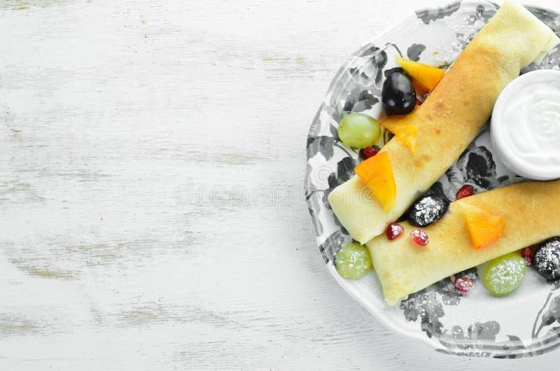 Блинчики с плодом и сметаной r На деревянной предпосылке стоковое изображение rf