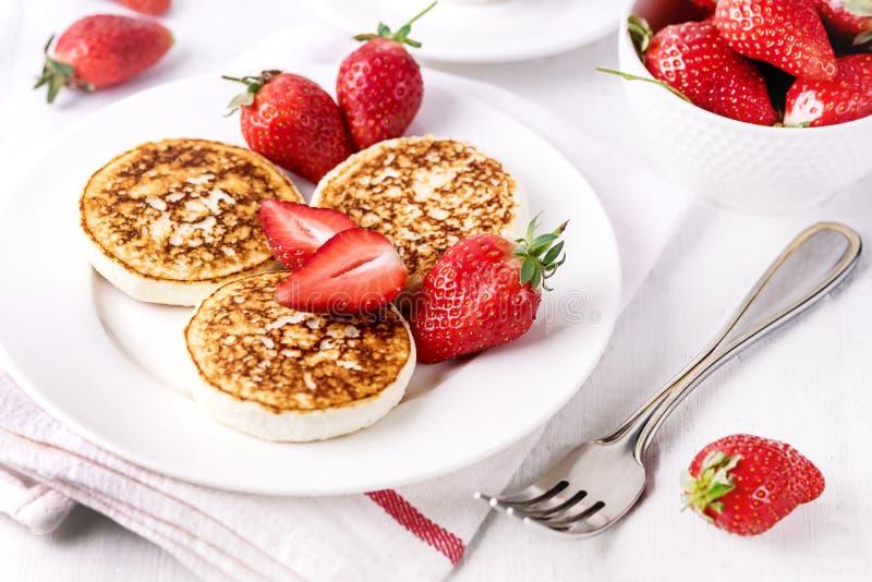 Блинчики творога ThreeTasty домодельные с клубниками на концепции завтрака завтрака Diey белой плиты вкусной здоровой стоковые фотографии rf