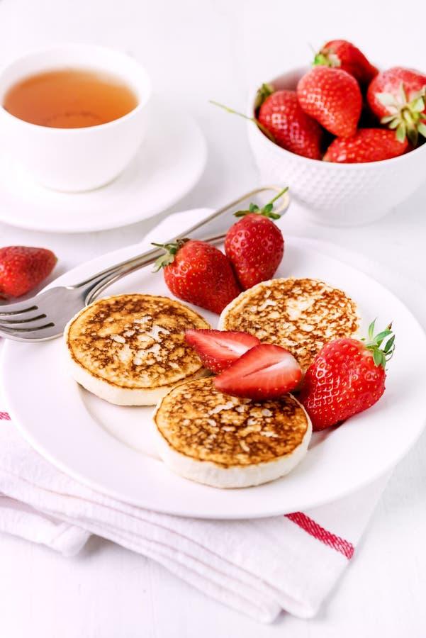Блинчики творога ThreeTasty домодельные с клубниками на концепции завтрака завтрака Diey белой плиты вкусной здоровой стоковая фотография rf