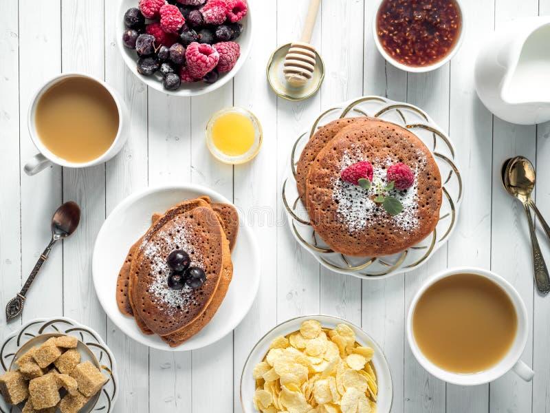 Блинчики шоколада завтрака с ягодами, чашкой кофе с сливк, медом и хлопьями Взгляд сверху стоковое изображение