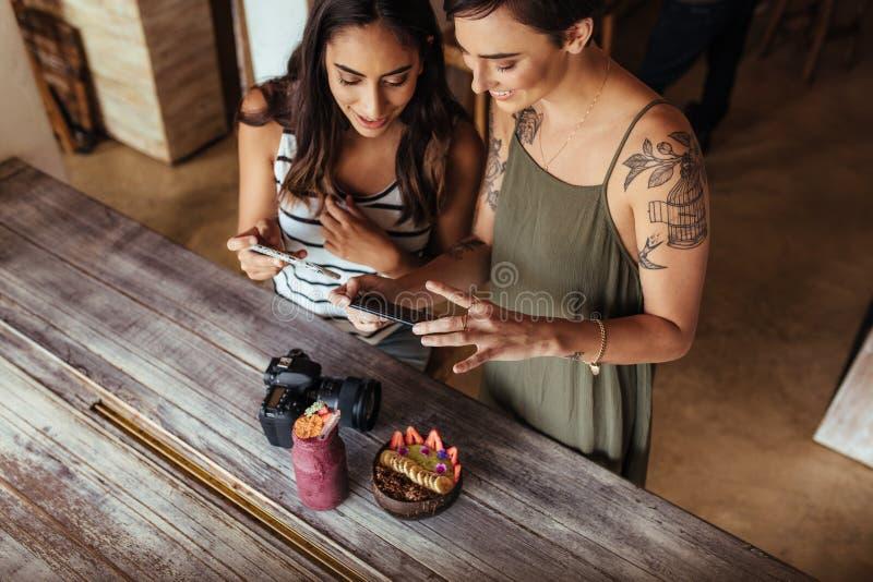 Блоггеры еды женщины фотографируя продукт питания стоковые фото