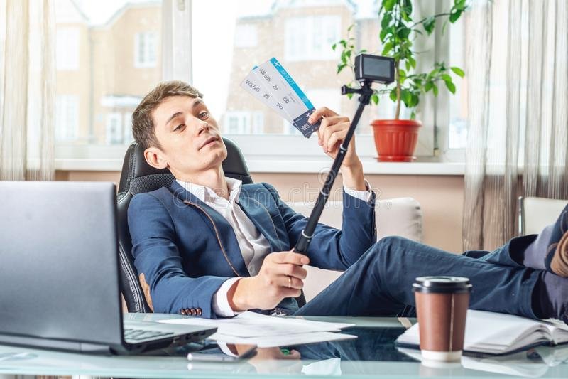 Блоггер бизнесмена с авиабилетами в его руках делит утеху путем записывать видео Концепция офиса на каникулах стоковые изображения