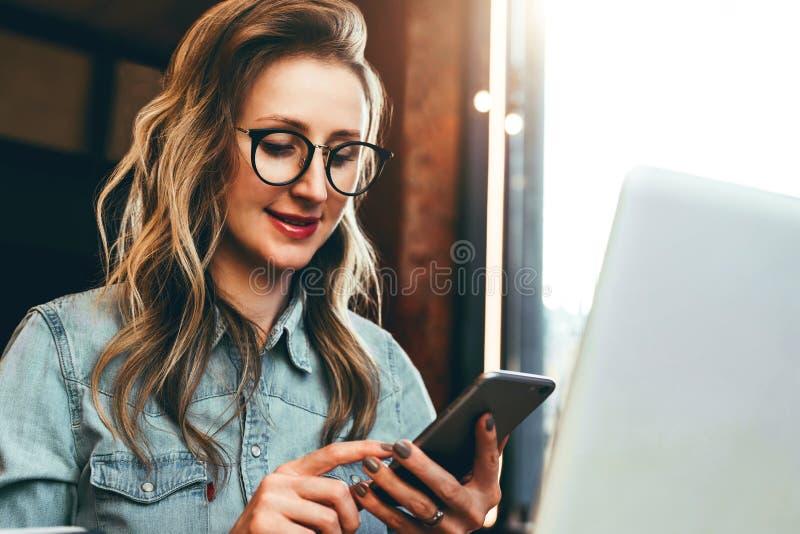 Блоггер девушки в ультрамодных стеклах сидит в кафе и использует smartphone, проверяет электронную почту, связывает с следующими, стоковые фотографии rf