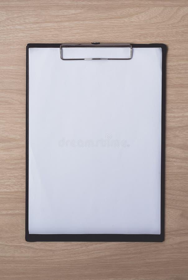 Блокнот или доска сзажимом для бумаги с пустой бумагой на коричневой деревянной таблице использующ для образования, предпосылка д стоковые фотографии rf