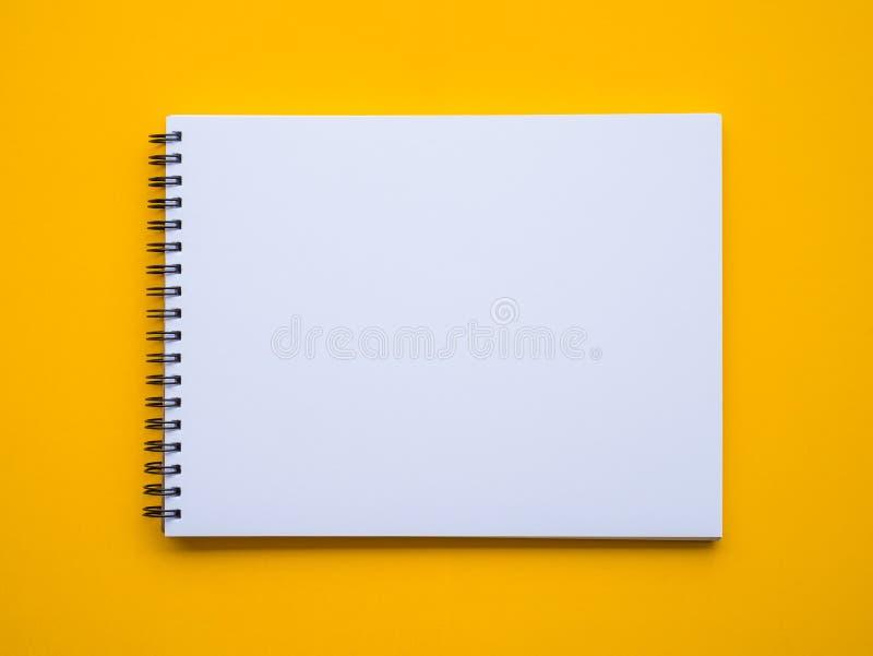 Блокнот на желтой предпосылке стоковое изображение rf