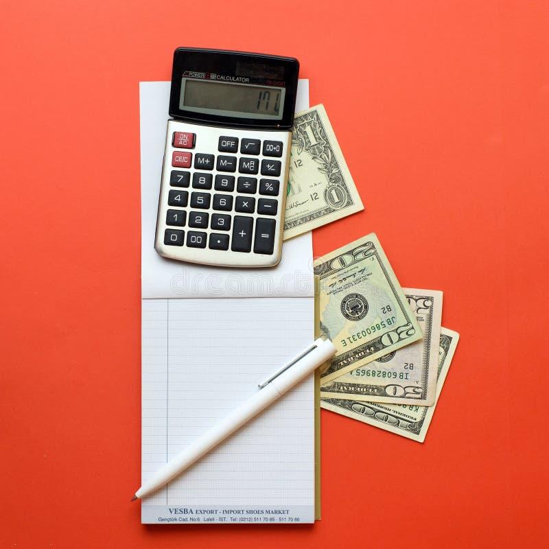 Блокнот с калькулятором, деньгами и ручкой на красной предпосылке Концепция дела и образования Взгляд сверху стоковые фотографии rf