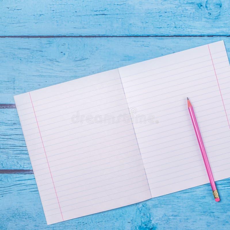 Блокнот с карандашем на деревянной предпосылке доски r Примите примечание продукта для книги с стоковые изображения rf