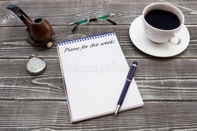 Блокнот с надписью, ручка: Планы ` на неделя: ` с чашкой кофе, трубой, стеклами и карманным вахтой стоковое фото