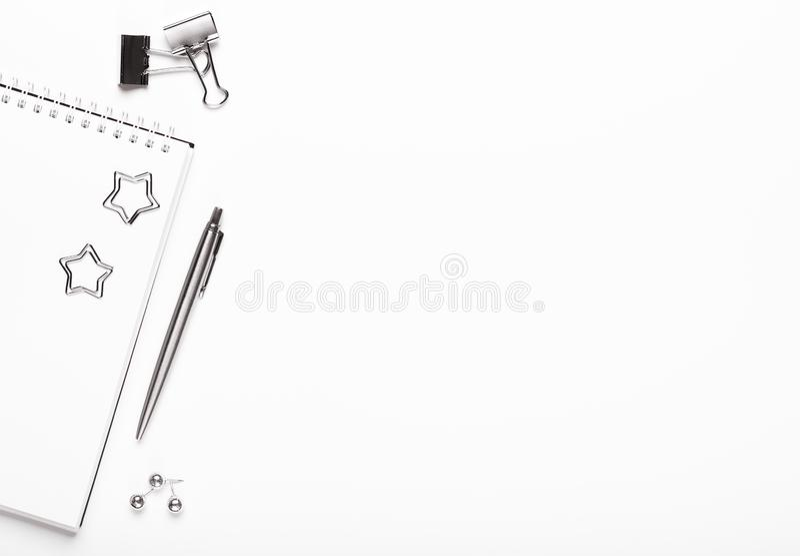 Блокнот с серебряными канцелярскими принадлежностями, бумажными зажимами, кнопками и ручкой на белой предпосылке Рабочий стол офи стоковая фотография rf