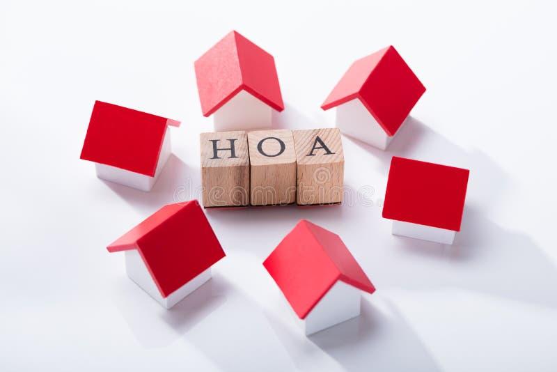 Блок ассоциации домовладельца деревянный окруженный с моделями дома стоковые фотографии rf