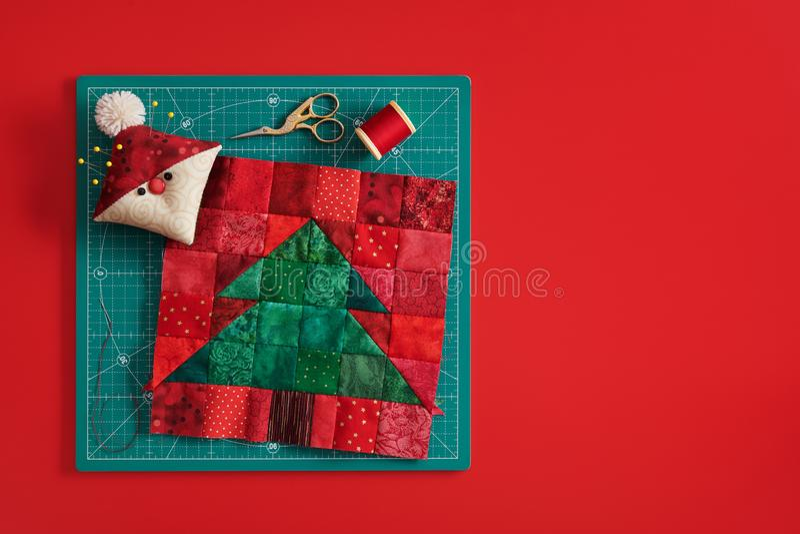 Блок заплатки рождественской елки, pincushion как Санта, ножницы, катышка потока на циновке ремесла, красной предпосылке стоковое изображение