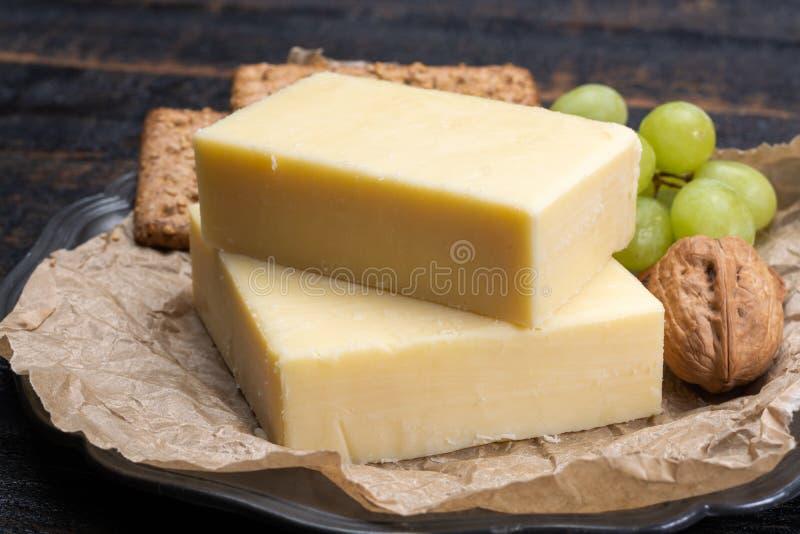 Блок постаретого сыра чеддера, самый популярный тип сыра внутри стоковые изображения