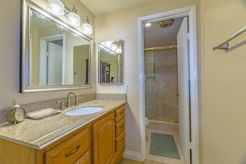 Блок тщеты с коричневыми деревянными шкафами и яркими светами внутри bathroom стоковые изображения rf
