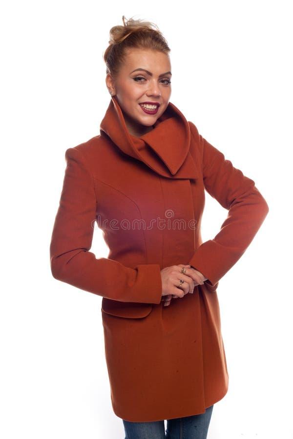 Блондинка в оранжевом пальто с кнопками и большими карманами стоковая фотография