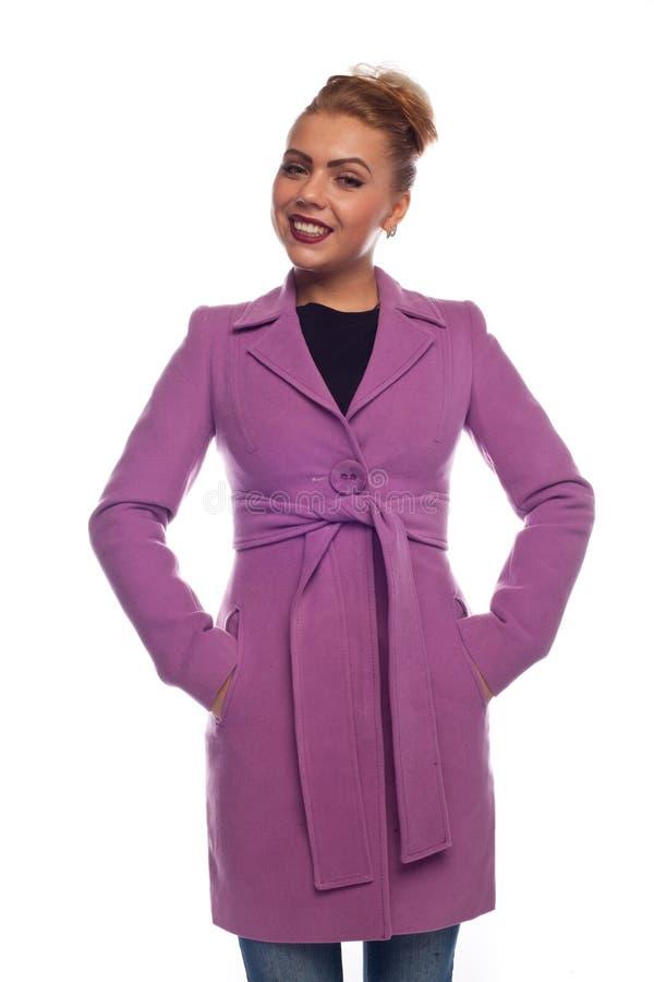 Блондинка в пальто сирени с поясом и кнопками стоковые фото