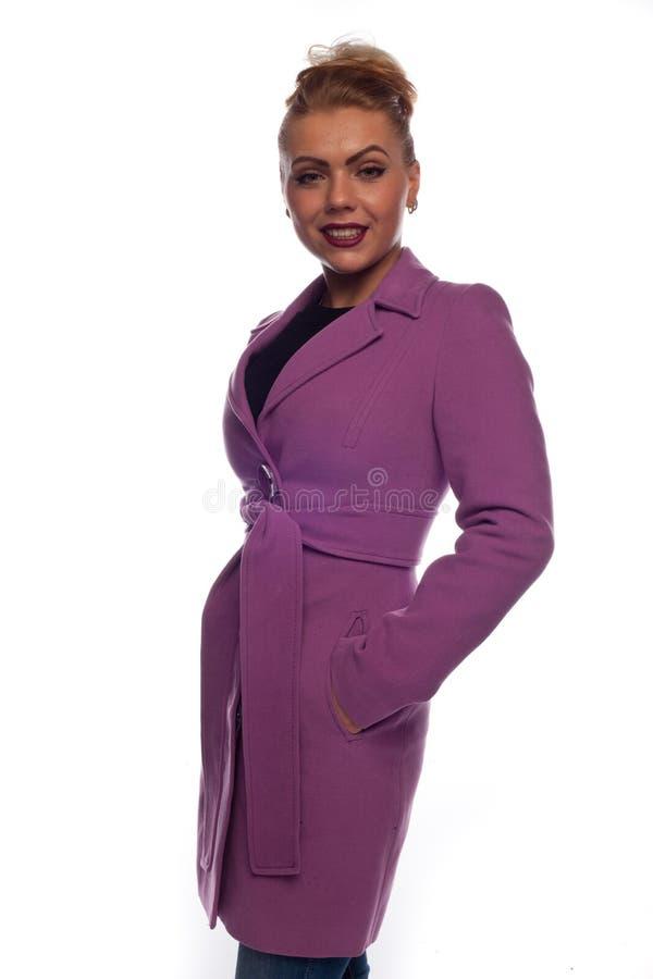 Блондинка в пальто сирени с поясом и кнопками стоковая фотография rf