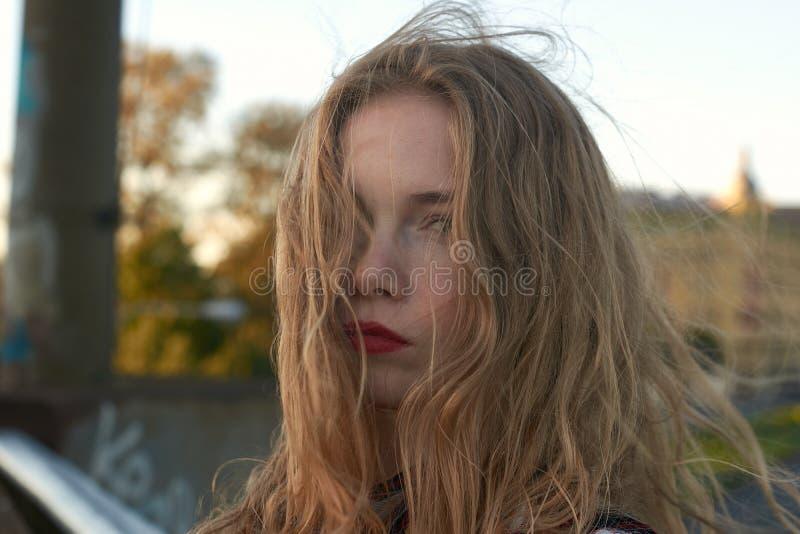 Блондинка в рубашке шотландки в ветреной погоде на железнодорожных путях стоковое фото