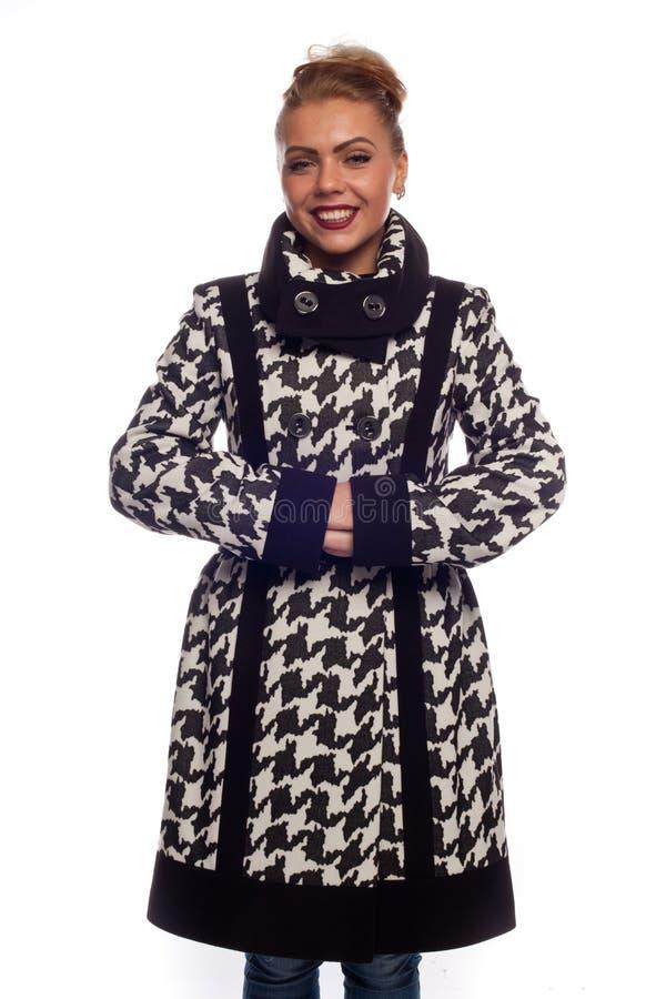 Блондинка в черно-белом пальто с большим воротником стоковое фото