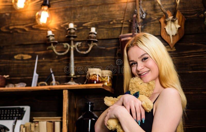 Блондинка дамы наслаждается отдыхом с плюшевым медвежонком Женщина на усмехаясь стороне ослабляя в деревянном интерьере Отдохните стоковое фото rf