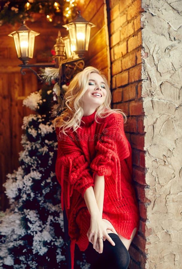 Блондинка женщины моды рождества сексуальная в красном свитере, имеющ потеху и представляющ против зимы рождественской елки и фон стоковое фото rf