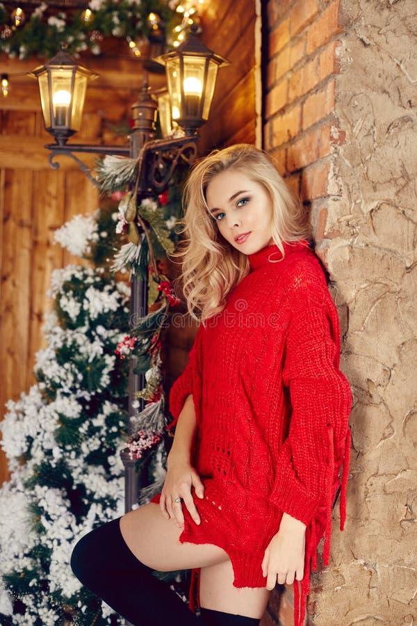 Блондинка женщины моды рождества сексуальная в красном свитере, имеющ потеху и представляющ против зимы рождественской елки и фон стоковые изображения