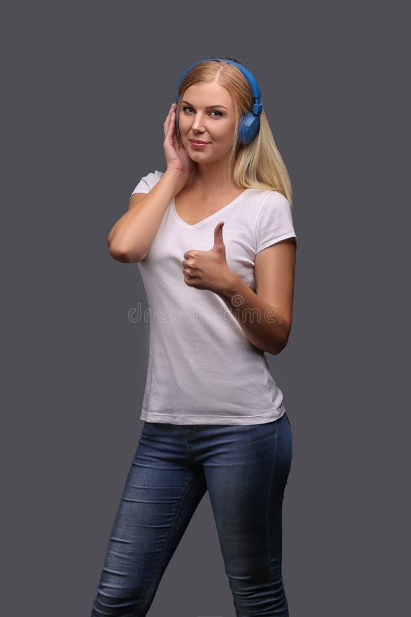 Блондинка маленькой девочки в голубых наушниках Слушающ, наслаждающся музыкой Изолят на серой предпосылке стоковые фото